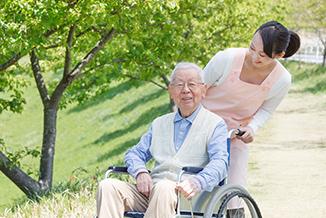 散歩する介護士と高齢者